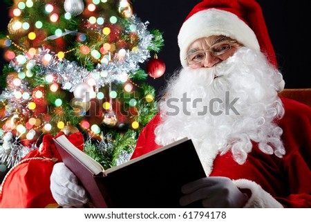 Santa sitting at the Christmas tree and reading a book - stock photo