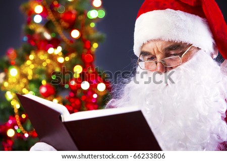 Santa sitting at the Christmas tree and reading a book - stock photo