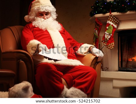 Santa sitting at the Christmas tree, holding Christmas letters and having a rest by the fireplace. Home decoration.
