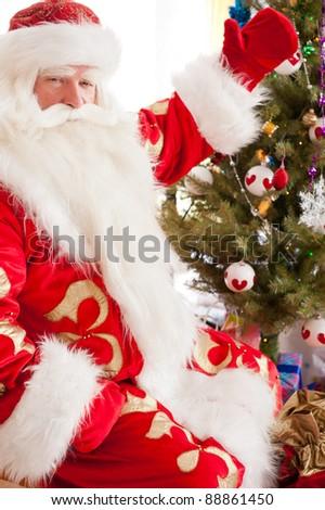 Santa sitting at the Christmas tree, near fireplace and looking at camera. Indoors - stock photo