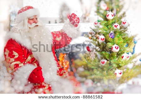 Santa sitting at the Christmas tree, near fireplace and looking at camera. Indoors. Magic snowy poster - stock photo