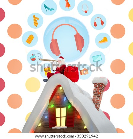 Santa sitting on roof of cottage against colorful polka dot pattern