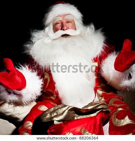 Santa sitting with a sack indoor at dark night room - stock photo