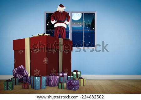 Santa standing on giant present against blue room with wooden floor - stock photo
