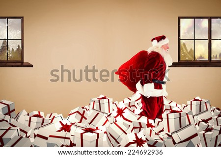 Santa walking on pile of gifts against room with wooden floor - stock photo