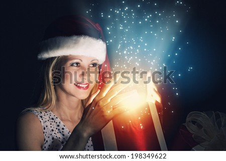 Santa woman in hat opening box with present - stock photo