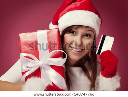 Santa woman with red gift box and credit card - stock photo