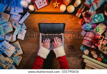 Santa working at desk and typing on a laptop surrounded by colorful Christmas gifts and letters, hands top view - stock photo
