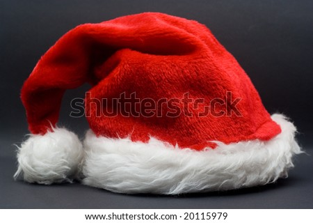 santas cap against the black background - christmas time - stock photo