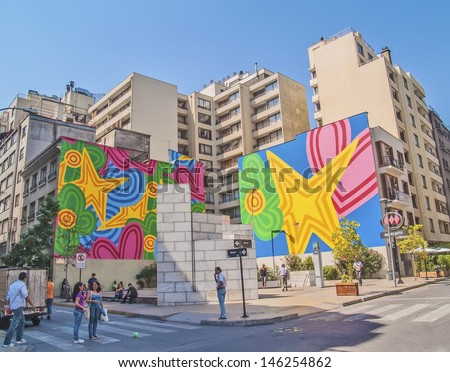 SANTIAGO, CHILE - FEBRUARY 15: Street on downtown with colorful graffiti and people walking and standing on February 15, 2011 in Santiago, Chile. 5.5 million population in Santiago. - stock photo