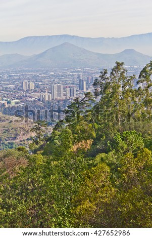 Santiago cityview from Cerro San Cristobal. Buldings can be seen in front of moutains and blue sky. Pollution is present too.