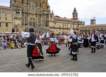 SANTIAGO DE COMPOSTELA, SPAIN - AUGUST 13, 2010: Dancers and pilgrims in the square before the cathedral in Santiago de Compostela, Galicia. Camino de Santiago is World Heritage Site by UNESCO - stock photo