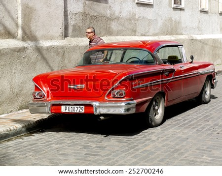 SANTIAGO DE CUBA, CUBA - DECEMBER 2:  an american vintage red car parked along a sidewalk ,on december 2, 2014, in Santiago de Cuba, Cuba  - stock photo