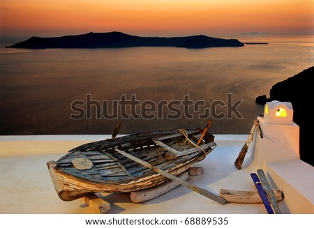 Santorini, a boat on a roof around sunset, in Firostefani village, right on the edge of the caldera. In the background you can see Thirassia island - stock photo