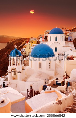 Santorini, classic view of blue dome churches at sunset. Oia Village, Greece. - stock photo