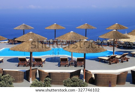 SANTORINI, GREECE - JULY 31, 2015: summer landscape with Mediterranean sea, pool and terrace in luxury resort, Santorini, Greece - stock photo