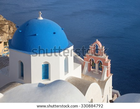 Santorini - The look to typically blue church cupolas with the little bell tower in Oia over the caldera. - stock photo