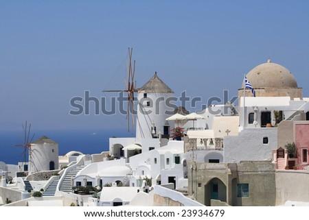 Santorini windmills and traditional white buldings - stock photo