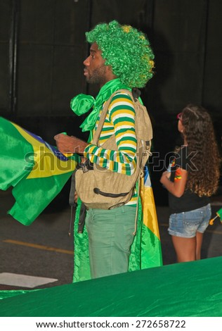 SAO PAULO, BRAZIL - APRIL 12, 2015: An unidentified man with green and yellow costume at protest against federal government corruption in Sao Paulo Brazil. - stock photo