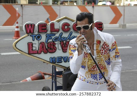 SAO PAULO, BRAZIL - FEBRUARY 08, 2015: An unidentified street musician imitates Elvis Presley dressed with typical vintage rock dress in Paulista Avenue at Sao Paulo Brazil. - stock photo