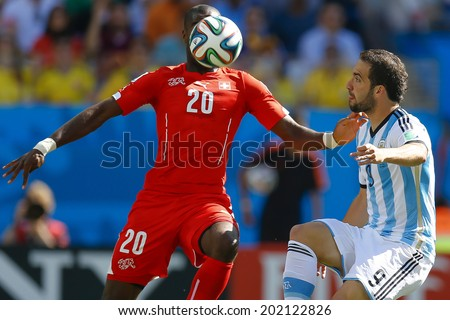 SAO PAULO, BRAZIL - July 1, 2014: Gonzalo Higuain of Argentina and Johan Djourou of Switzerland during the game between Argentina and Switzerland at Arena Corinthians. No Use in Brazil.