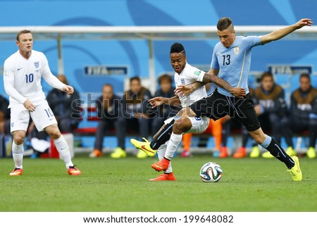 SAO PAULO, BRAZIL - June 19, 2014: Jose Gimenez of Uruguay and Raheem Sterling of England compete for the ball during the game between Uruguay and England at Arena Corinthians. No Use in Brazil. - stock photo