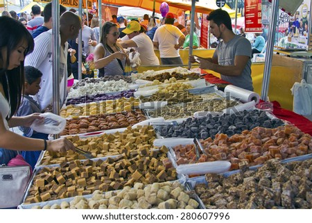 SAO PAULO, BRAZIL - MAY 17, 2015: An unidentified group of people in the hand made sweet stand at a street fair market in Sao Paulo.  - stock photo