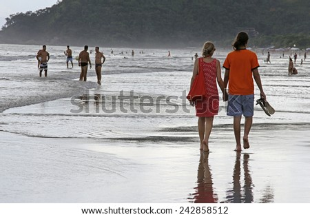 SAO SEBASTIAO, BRAZIL - JANUARY 04, 2015: An unidentified couple walking along a crowed beach at sunset in Brazil in the summer. - stock photo