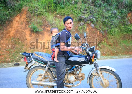 SAPA, VIETNAM - October 8, 2014: unidentified man with his small baby strapped behind his back sitting on motorbike