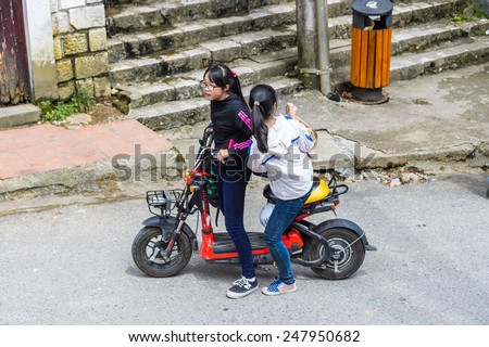 SAPA, VIETNAM - SEP 22, 2014: Unidentified Hmong girls on a motorbike in Sapa. Hmong is on of the minority eethnic group in Vietnam