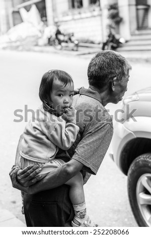 SAPA, VIETNAM - SEP 22, 2014: Unidentified Hmong little girl on her father back in Sapa. Hmong is on of the minority eethnic group in Vietnam