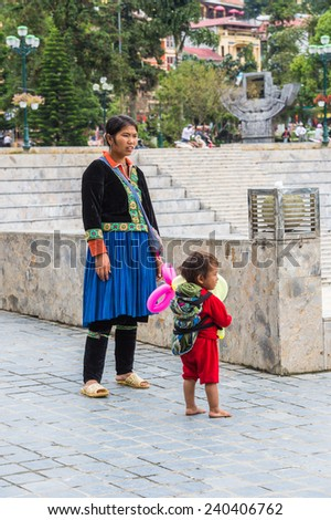 SAPA, VIETNAM - SEP 20, 2014: Unidentified Hmong woman in a traditional costume and her little children. Hmong people is a minority ethnic group living in Sapa