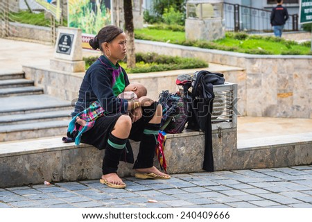 SAPA, VIETNAM - SEP 20, 2014: Unidentified Hmong woman in a traditional costume and her little baby on her arms. Hmong people is a minority ethnic group living in Sapa