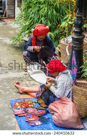 SAPA, VIETNAM - SEP 20, 2014: Unidentified Hmong woman in a traditional dress sews in the street. Hmong people is a minority ethnic group living in Sapa