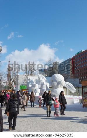 SAPPORO, JAPAN - FEB. 8 : Tourists at Sapporo Snow Festival site on February 8, 2012 in Sapporo, Hokkaido, japan. Sapporo Snow Festival is held annually at Sapporo Odori Park. - stock photo