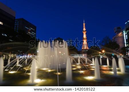 SAPPORO, JAPAN - JUNE. 12 : Night scene of Sapporo TV Tower and the West 3 Fountain on June 12, 2013 in Sapporo, Hokkaido, japan. The Tower and Fountain are located at Sapporo Odori Park. - stock photo