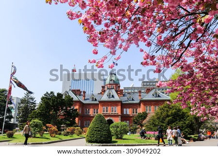 SAPPORO, JAPAN- MAY 6, 2015 : Former Hokkaido Government Office made of red bricks and its garden with Sakura or Cherry Blossom blooming during Japan Golden Week 2015.  - stock photo