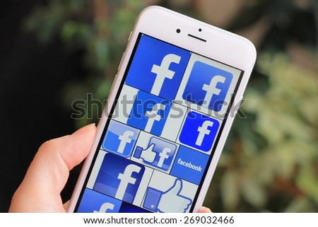SARAJEVO , BOSNIA AND HERZEGOVINA - APRIL 12 , 2015: Woman watch Facebook icons on Apple iPhone 6. Facebook is largest and most popular social networking site in the world. - stock photo