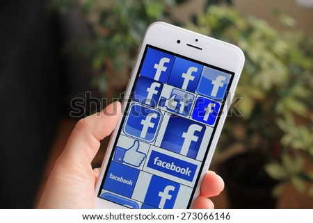 SARAJEVO , BOSNIA AND HERZEGOVINA - APRIL 27, 2015: Woman watch Facebook icons on Apple iPhone 6. Facebook is largest and most popular social networking site in the world. - stock photo