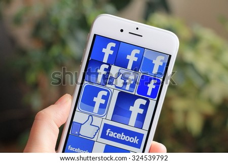 SARAJEVO , BOSNIA AND HERZEGOVINA - APRIL 27 , 2015: Woman watch Facebook icons on Apple iPhone 6. Facebook is largest and most popular social networking site in the world. - stock photo