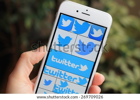 SARAJEVO , BOSNIA AND HERZEGOVINA - APRIL 05, 2015: Woman with Twitter icons on Apple iPhone 6. Twitter is largest and most popular social networking site in the world. - stock photo