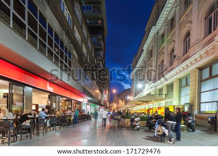 SARAJEVO, BOSNIA AND HERZEGOVINA - AUGUST 13, 2012: Street at night crowded with tourists - with motion blur. - stock photo