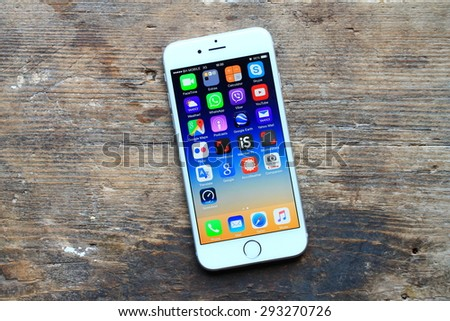 SARAJEVO , BOSNIA AND HERZEGOVINA - JULY 04 , 2015: New gray iPhone 6 with colorful screen on the wooden table. iPhone 6 was created and developed by the Apple inc. - stock photo