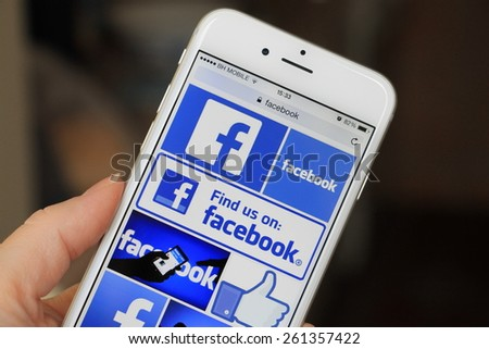 SARAJEVO , BOSNIA AND HERZEGOVINA - MARCH 17, 2015: Woman watch Facebook icons on Apple iPhone 6. Facebook is largest and most popular social networking site in the world. - stock photo