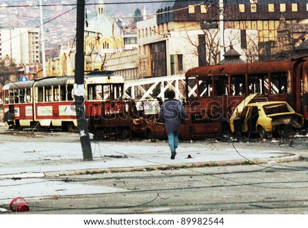 SARAJEVO, BOSNIA - APR 4: A man braves sniper fire to run through destroyed trams and cars in Sarajevo, Bosnia, on Sunday, April 4, 1993. - stock photo