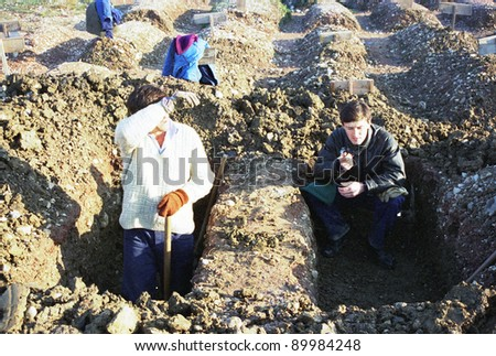 SARAJEVO, BOSNIA - JAN 15: Workers dig fresh graves in the shadow of the 1984 Winter Olympic stadium at the Lion cemetery in Sarajevo, Bosnia, on Monday, January 15, 1993. - stock photo
