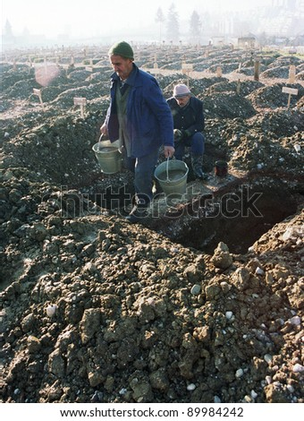 SARAJEVO, BOSNIA - JAN 15: Workers remove water from freshly dug graves at the Lion cemetery in Sarajevo, Bosnia, on Monday, January 15, 1993. - stock photo