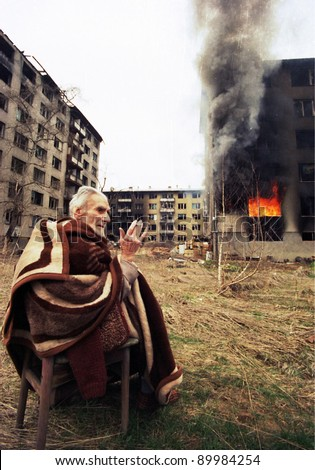 SARAJEVO, BOSNIA - MAR 18: An ethnic Croatian man prays outside his burning apartment on the last day of the Serbian siege in Sarajevo, Bosnia, on Monday, March 18, 1996. - stock photo
