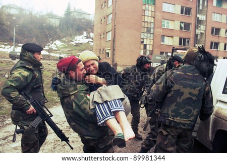 SARAJEVO, BOSNIA - MAR 18: Italian army troops, in Bosnia as part of the United Nation's  UNPROFOR, help an injured woman to safety in Sarajevo, Bosnia, on Monday, March 18, 1996. - stock photo