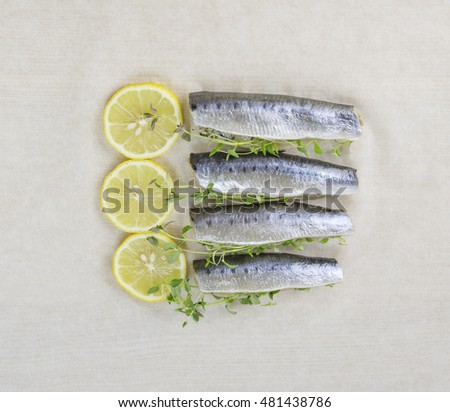 sardines fish with lemon and thyme herb on paper